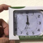 100均ダイソーの目覚まし時計の箱を持つ